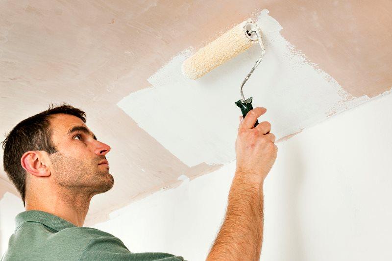 человек красит потолок